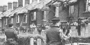 British soldiers look on at burned out houses in Belfast in the early years of the Troubles.